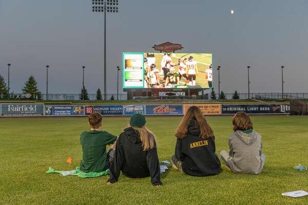 Fans watch on the big screen at Dow Diamond as H. H. Dow High School plays Saginaw High School in football Friday, Sept. 25, 2020 in Midland. (Katy Kildee/kkildee@mdn.net)