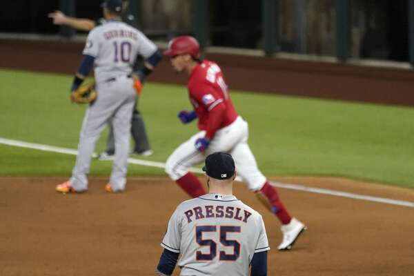 Houston Astros relief pitcher Ryan Pressly (55) looks on as Texas Rangers' Ronald Guzman, center, rounds the bases after hitting a solo home run off Pressly in the ninth inning of a baseball game in Arlington, Texas, Friday, Sept. 25, 2020. (AP Photo/Tony Gutierrez)