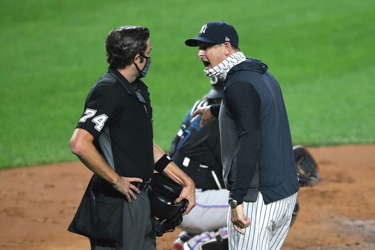 NEW YORK, NEW YORK - SEPTEMBER 25: Manager Aaron Boone #17 of the New York Yankees exchanges words with umpire John Tumpane #74 during the first inning against the Miami Marlins at Yankee Stadium on September 25, 2020 in the Bronx borough of New York City. (Photo by Sarah Stier/Getty Images)