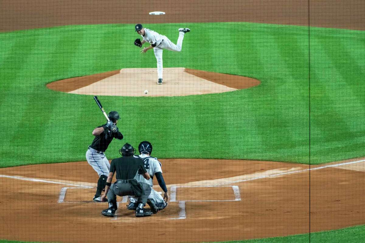 New York Yankees starting pitcher J.A. Happ, top, pitches to Miami Marlins' Jon Berti, bottom left, during the first inning of a baseball game at Yankee Stadium, Friday, Sept. 25, 2020, in New York. (AP Photo/Corey Sipkin)