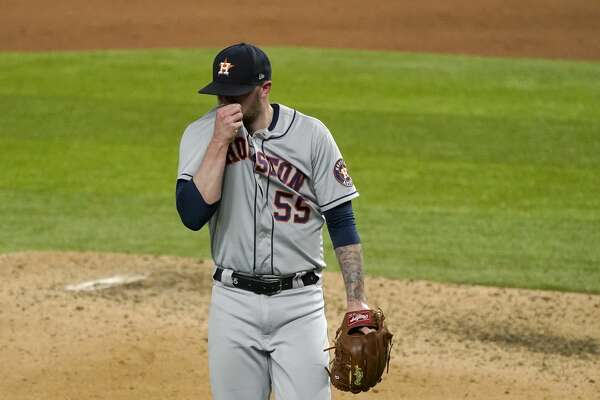Houston Astros' Ryan Pressly (55) wipes his face as he walks to the dugout in the ninth inning of a baseball game against the Texas Rangers in Arlington, Texas, Friday, Sept. 25, 2020. Pressly gave up a tying solo home run to Rangers' Ronald Guzman in the inning. (AP Photo/Tony Gutierrez)