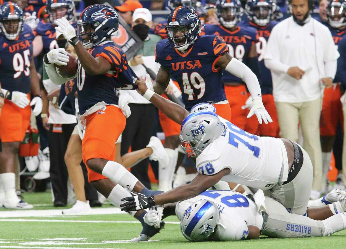 UTSA safety Donyai Taylor tries to return an interception as Middle Tennessee offensive lineman Dorian Hinton holds on tight.