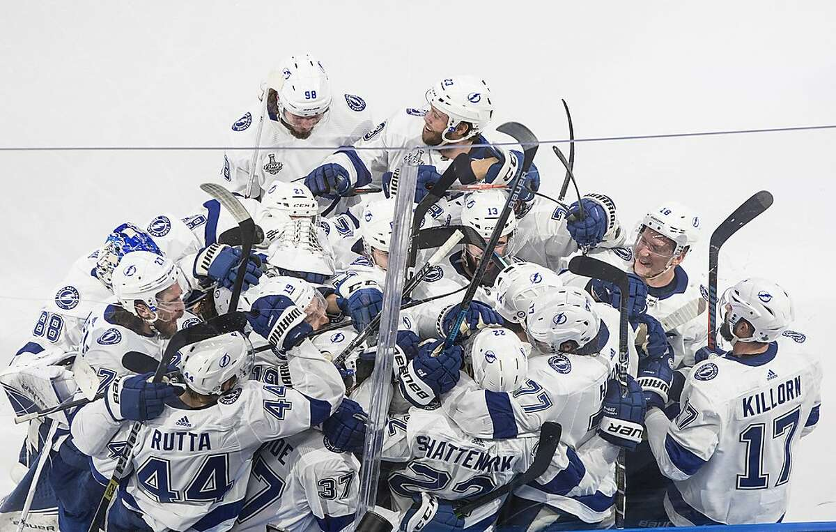 Tampa Bay Lightning players celebrate an overtime win against the Dallas Stars in Game 4 of the NHL hockey Stanley Cup Final, Friday, Sept. 25, 2020, in Edmonton, Alberta. (Jason Franson/The Canadian Press via AP)