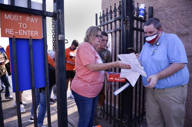 Gate attendant Zach Davis, right, checks fans' tickets before a high school football game between Deer Park and La Porte, Friday, Sept. 25, 2020, in La Porte. Photo: Eric Christian Smith/Contributor