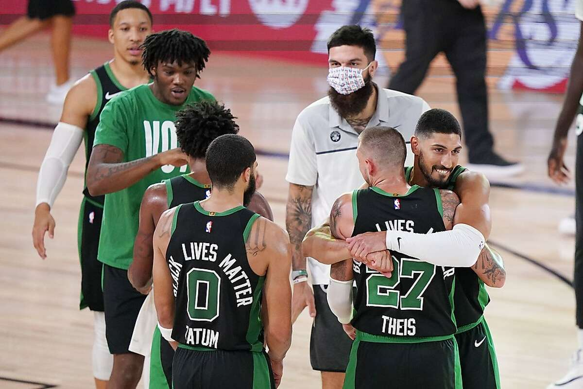 Boston Celtics players celebrate after beating the Miami Heat 121-108 in the Western Conference finals Game 5 in Lake Buena Vista, Fla., on Friday. Miami leads the series 3-2.