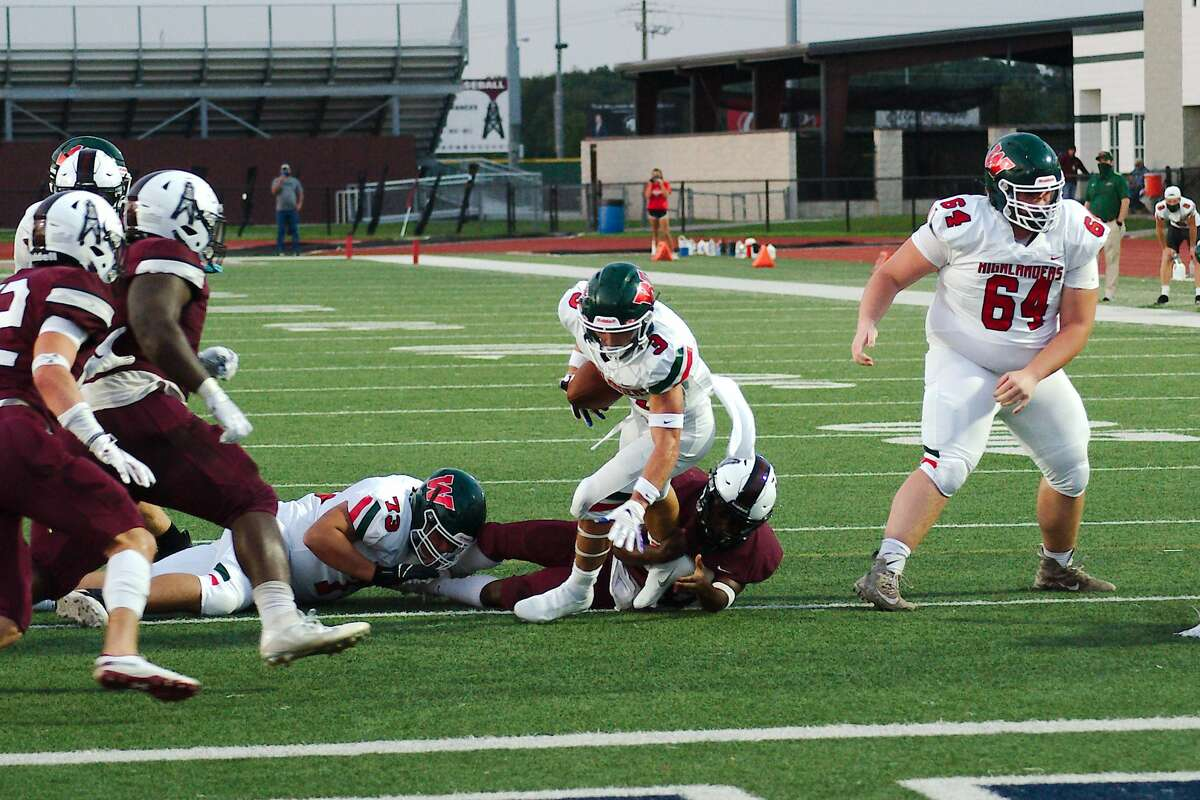 The Woodland's Jack Calhoun (3) fights for yardage against Pearland Friday at The Rig.