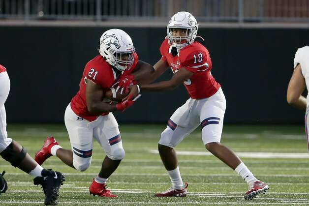 Manvel quarterback Cornelius Banks III (10) hands off to De'monte' Seymore (21) during the first half of their scrimmage against Dickinson at Freedom Field Sept. 25, 2020 in Arcola, TX. Photo: Michael Wyke/Contributor / © 2020 Houston Chronicle
