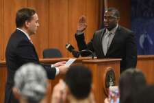 Then-First Selectman and Police Commissioner Peter Tesei, left, swears in Officer Michael Hall at Town Hall in Greenwich, Conn. Monday, Dec. 29, 2014.