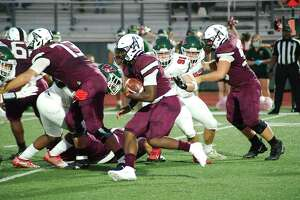 Pearland's Darius Hale (4) looks for running room against The Woodlands Friday at The Rig.