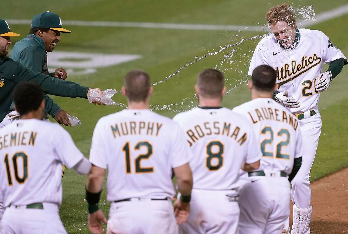 Mark Canha celebrates with teammates after he hit a two-run walk off home run Friday in Oakland.
