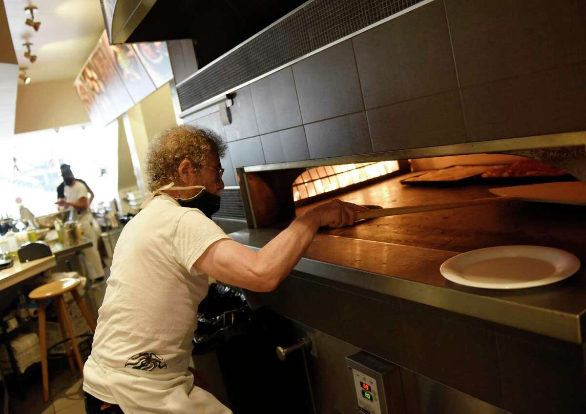 Co-owner Louis Termini puts a pizza in the oven at Ignazio's Pizza in Greenwich on Tuesday. Located at 30 Greenwich Ave., the Greenwich restaurant joins other Ignazio's locations in Brooklyn and Westport.