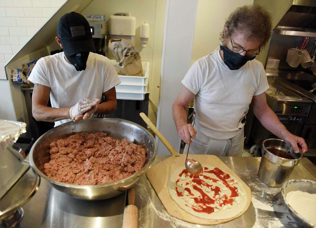 Oswaldo Ramirez, left, makes meatballs while co-owner Louis Termini makes a pizza at Ignazio's Pizza in Greenwich on Tuesday. Located at 30 Greenwich Ave., the Greenwich restaurant joins other Ignazio's locations in Brooklyn and Westport.