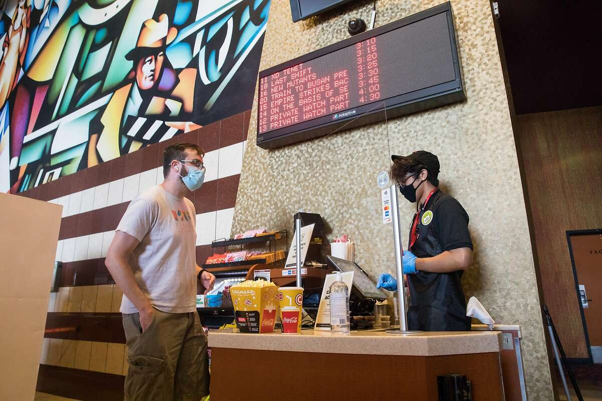 Customer Caleb Mayfield purchases a popcorn and soda from cashier Carlos Zuniga. For the first time since March the Century at Tanforan movie theater opened to the public for screenings on Sept. 25, 2020. Movie theaters in San Mateo County are now allowed to have patrons watch movie screenings, but capacity is capped at 25% because of COVID-19 restrictions.