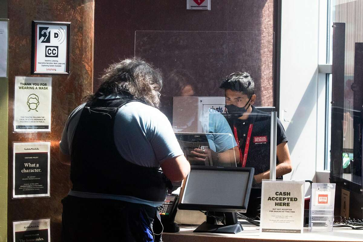 Cinemark employee Vincent Maliga helps a customer buy movie tickets. For the first time since March the Century at Tanforan movie theater opened to the public for screenings on September 25, 2020. Movie theaters in San Mateo County are now allowed to have patrons watch movie screenings, but capacity is capped at 25 percent due to COVID-19 coronavirus restrictions.