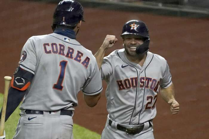 Houston Astros' Carlos Correa (1) celebrates with Jose Altuve, right, who scored on a Yuli Gurriel single in the eighth inning of a baseball game against the Texas Rangers in Arlington, Texas, Friday, Sept. 25, 2020. (AP Photo/Tony Gutierrez)