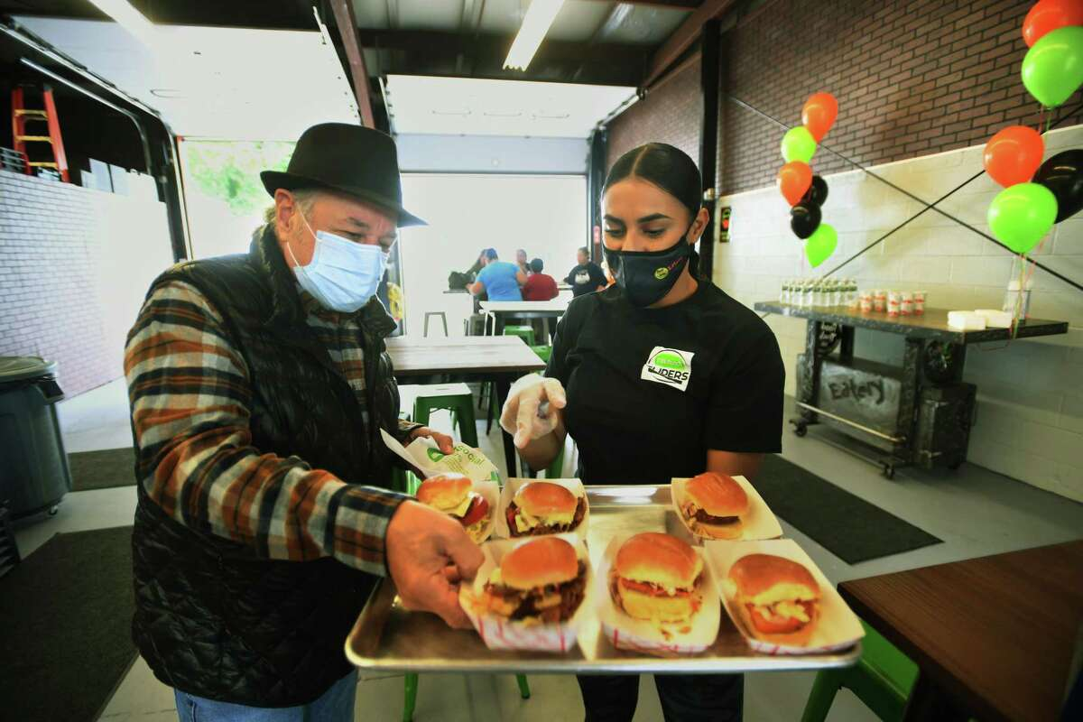 Ansonia Alderman Joe Cassetti tries the sliders from Tiffany Nieves during the grand opening of Food Trucks & Co. Eatery on Howard Avenue in Ansonia, Conn. on Thursday, September 24, 2020.