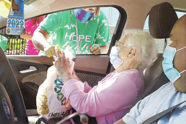 One of the 235 cars full of cancer survivors stops to get their gift bag and popcorn Friday outside the OSF HealthCare Moeller Cancer Center in Alton. There were single and multiple cancer survivors who drove through and were met with an enthusiastic welcome from staff.