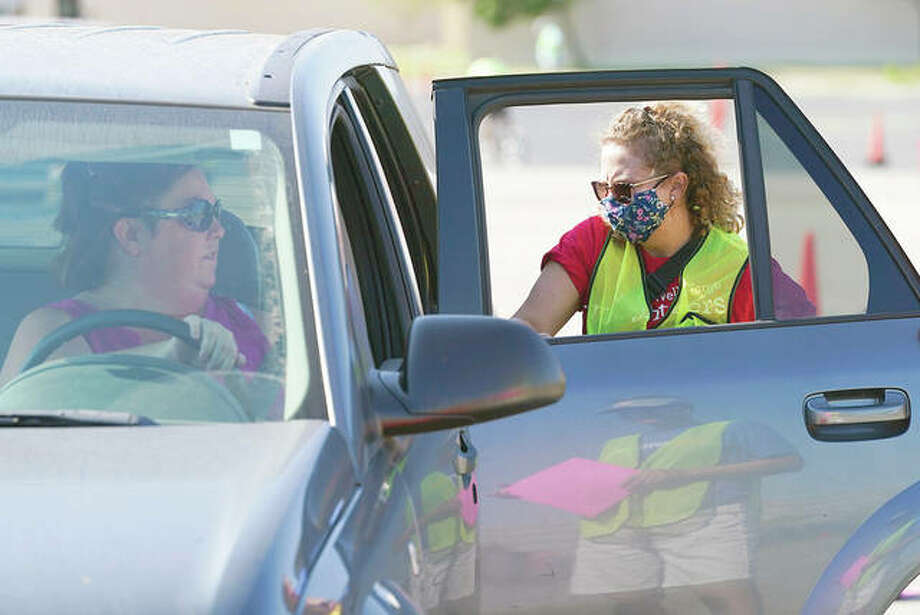 A volunteer loads a vehicle at a drive-up produce giveaway. Photo: Charlie Neibergall | AP
