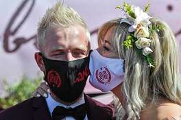 Many wedding venues require guests to wear face masks as they walk down the aisle.