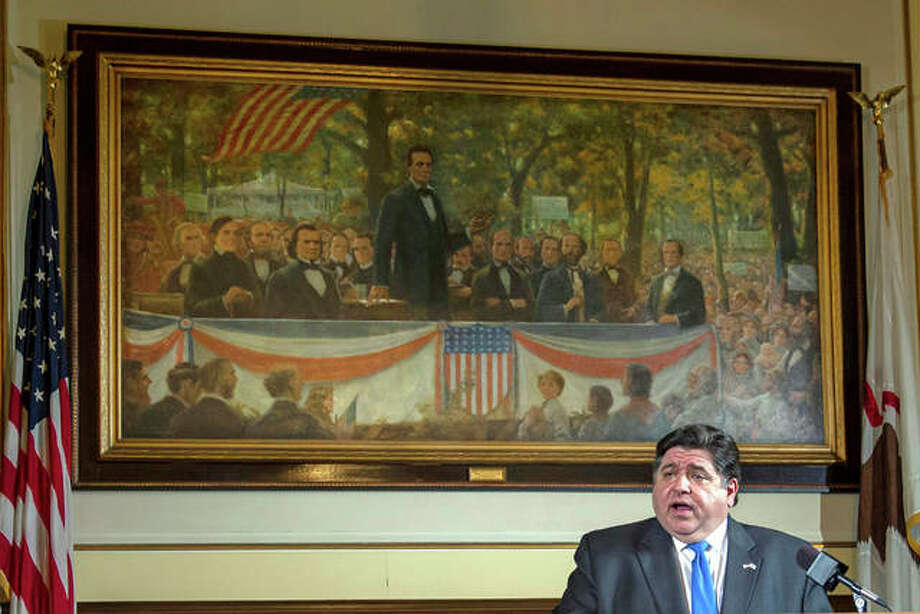 In this May 22 file photo, Gov. J.B. Pritzker answers questions from the media, from his office at the Illinois State Capitol, in Springfield in front of a painting painting depicting a political debate in Charleston on Sept. 18, 1858 between Stephen A. Douglas and Abraham Lincoln.