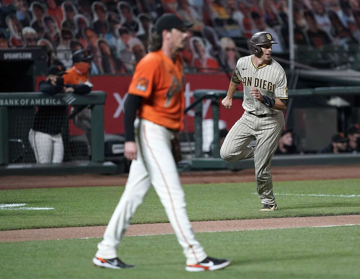 San Diego Padres' Jason Castro, right, rounds third base to score on a single by Trent Grisham as San Francisco Giants pitcher Jeff Samardzija, left, looks to the outfield during the second inning of the second game of a baseball doubleheader Friday, Sept. 25, 2020, in San Francisco. (AP Photo/Tony Avelar)