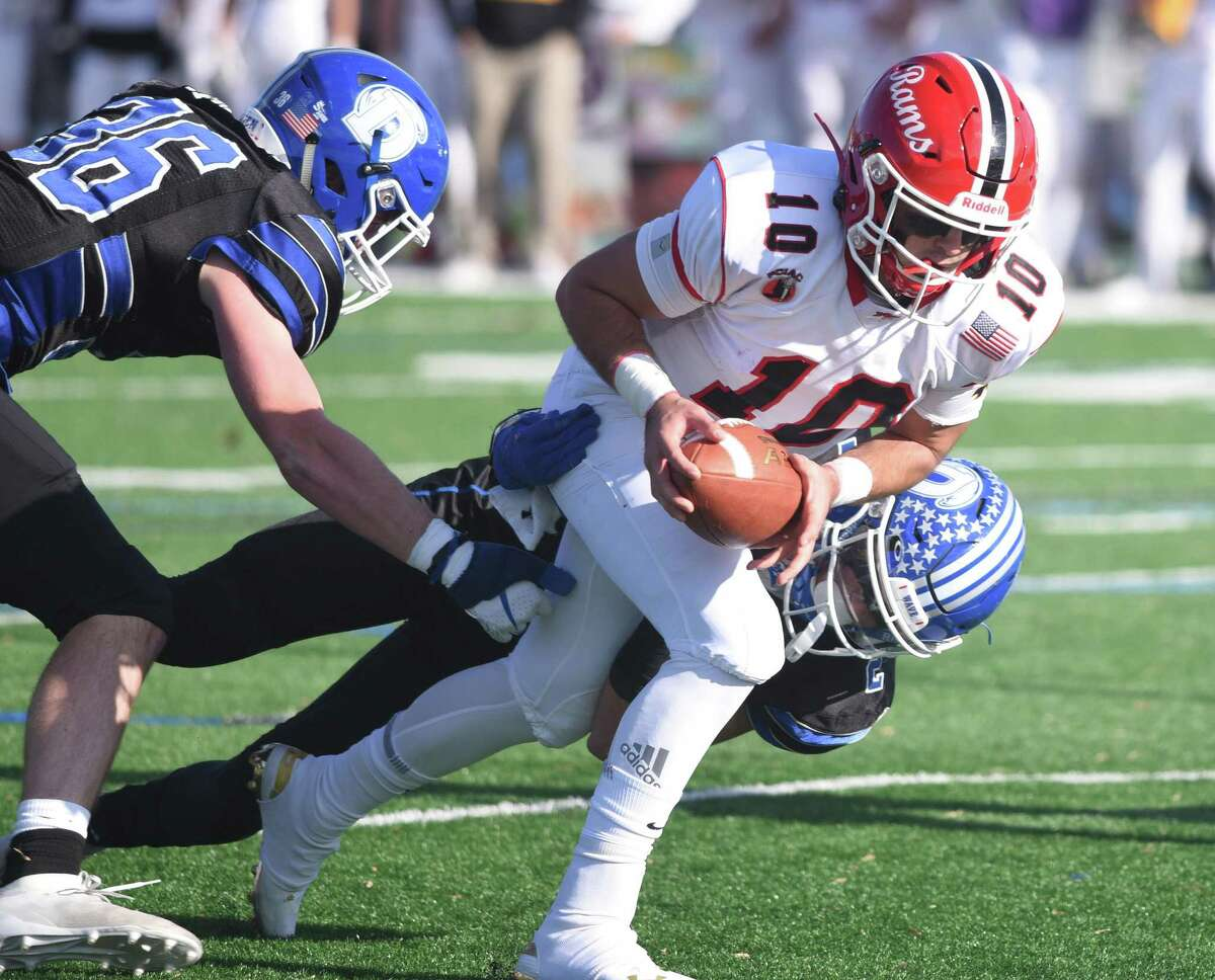 New Canaan quarterback Drew Pyne (10) runs to the end zone as the Darien defense attempts to bring him down during the annual Turkey Bowl football game between Darien and New Canaan at Darien High School on Thursday, Nov. 28, 2019.