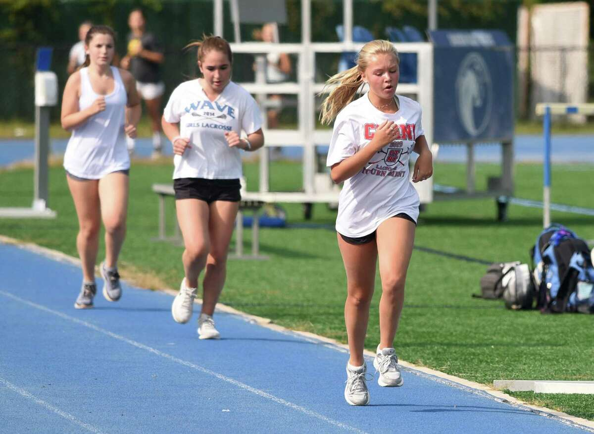 Darien girls cross country athletes run on the high school track during the preseason for Blue Wave athletics on Tuesday, Sept. 15.