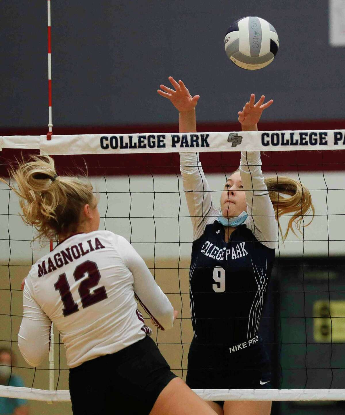 College Park's Koralyn Owens (9) blocks a shot by Magnolia's Sydney Gentry (12) during the first set of a non-district high school volleyball match at College Park High School, Saturday, Sept. 26, 2020, in The Woodlands.