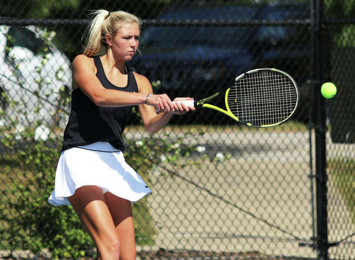 Edwardsville senior Emma Herman returns a shot during her No. 5 singles match against Marquette Catholic on Saturday afternoon at Moore Park's Simpson Tennis Center in Alton.