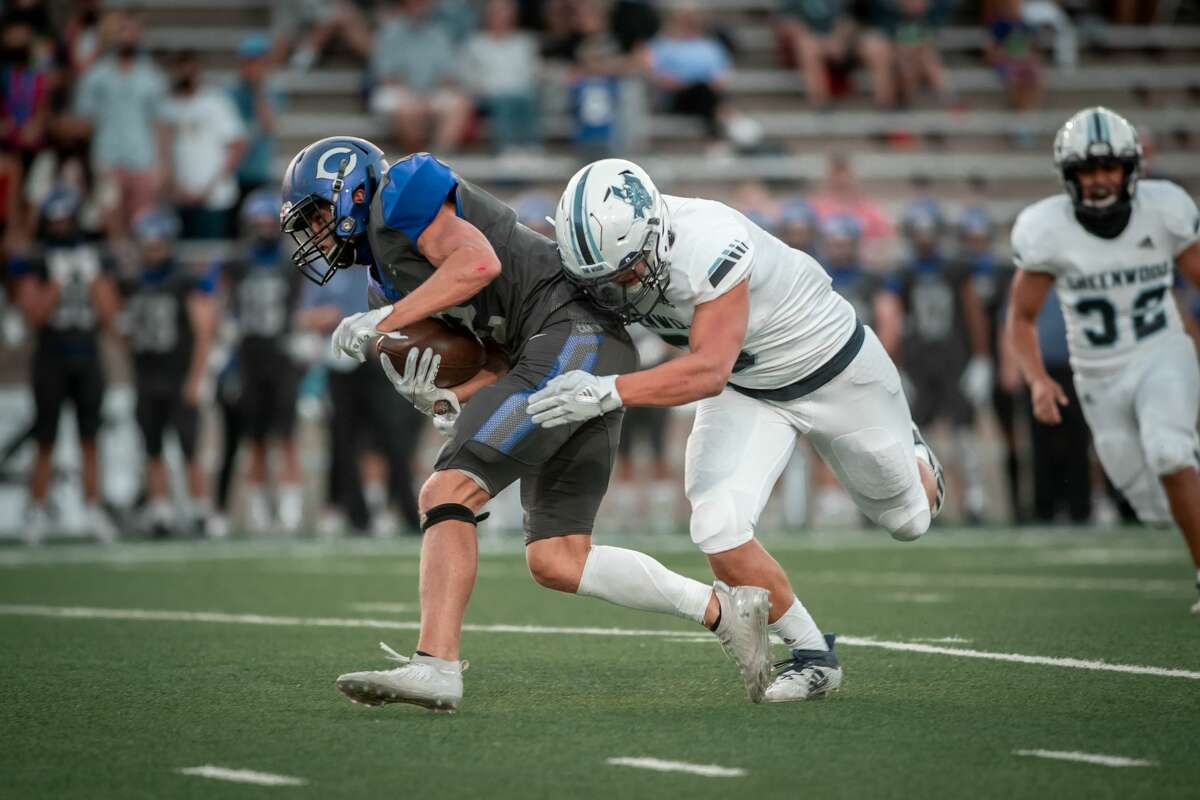 A Greenwood defender makes a tackles against Canyon on Friday night.