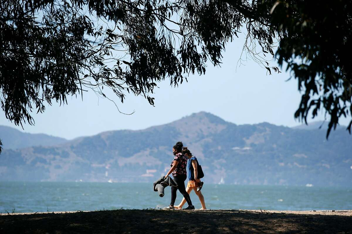 Visitors walk on the Albany Waterfront Trail on Saturday, before smoky air returns.