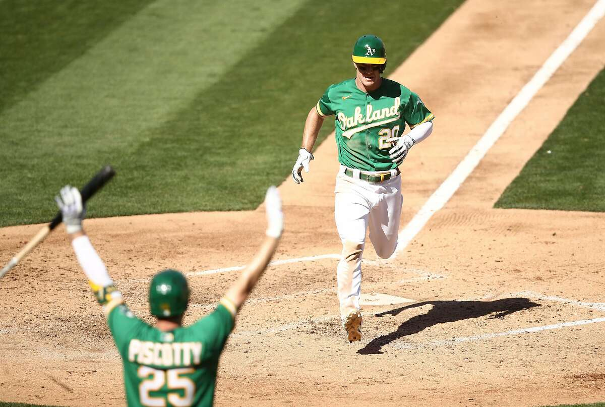 OAKLAND, CALIFORNIA - SEPTEMBER 26: Mark Canha #20 of the Oakland Athletics runs home to score as Stephen Piscotty #25 raises hands in the foreground in the fourth inning of their game against the Seattle Mariners in game one of their double header at RingCentral Coliseum on September 26, 2020 in Oakland, California. (Photo by Ezra Shaw/Getty Images)