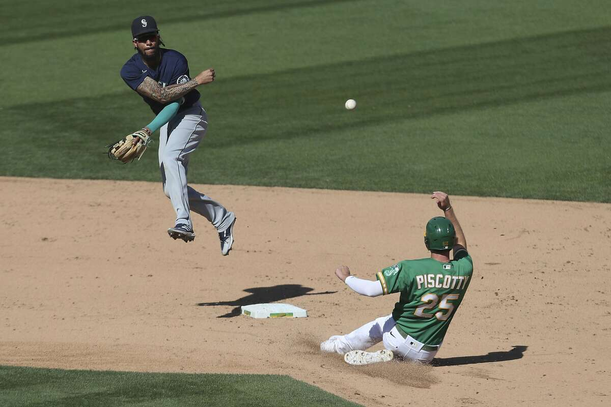 Mariners shortstop J.P. Crawford throws to first as the A's Stephen Piscotty slides into second base on a double play hit into by Jake Lamb during the seventh inning of Game 1 of a doubleheader on Saturday at the Coliseum.