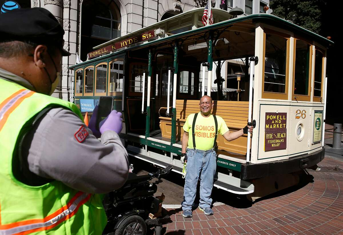 Cable car gripman Val Lupiz (left) snaps a picture of Luis Castillo at Powell and Market streets in San Francisco as part of a Muni plan to put a cable car on the turntable on Saturdays, Tuesdays and Thursdays for photo opportunities, but not rides.