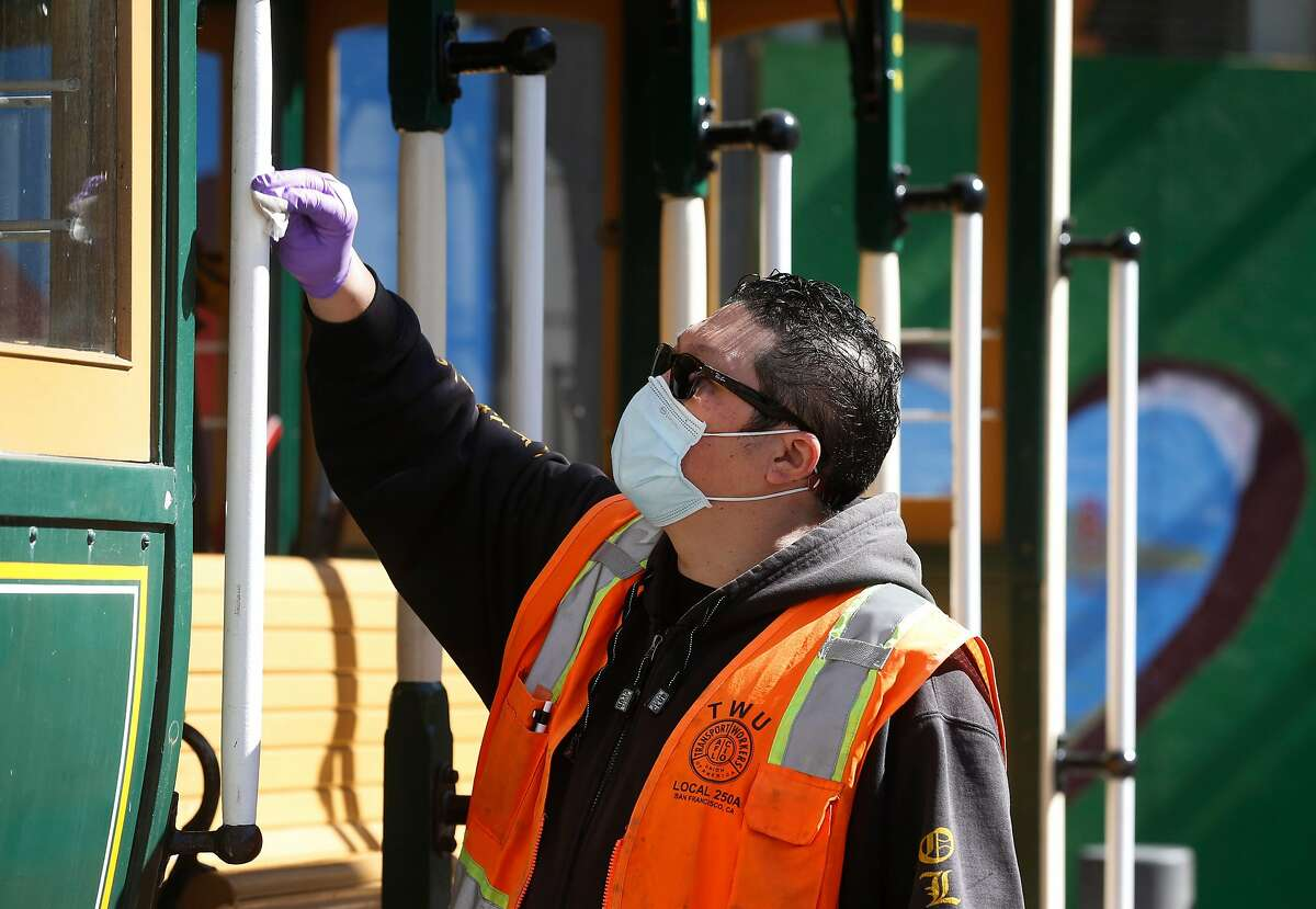 Conductor Vince Lee sanitizes a cable car displayed on the turntable at Powell and Market streets in San Francisco.