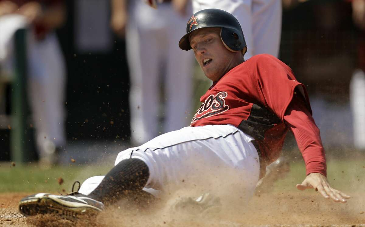 Houston Astros' Hunter Pence slides home to score on a single by Carlos Lee during the fifth inning of a spring training baseball game against the New York Yankees Saturday, March 20, 2010 in Kissimmee, Fla. (AP Photo/Charlie Riedel)
