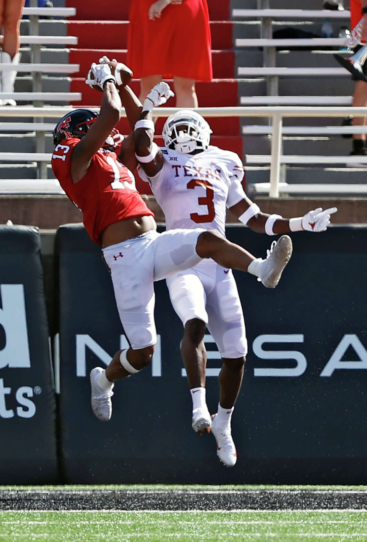 Texas Tech's Erik Ezukanma (13) catches a touchdown pass around Texas' Jalen Green (3) during the first half of an NCAA college football game Saturday, Sept. 26, 2020, in Lubbock, Texas. (Brad Tollefson/Lubbock Avalanche-Journal via AP)