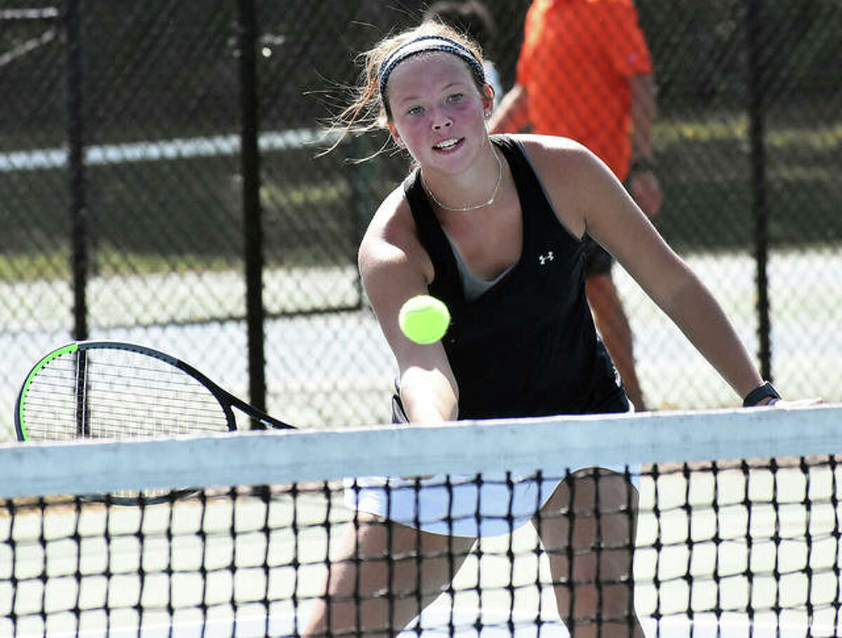Edwardsville senior Morgan Marshall taps the ball over the net during her singles match against Marquette on Saturday in Alton.