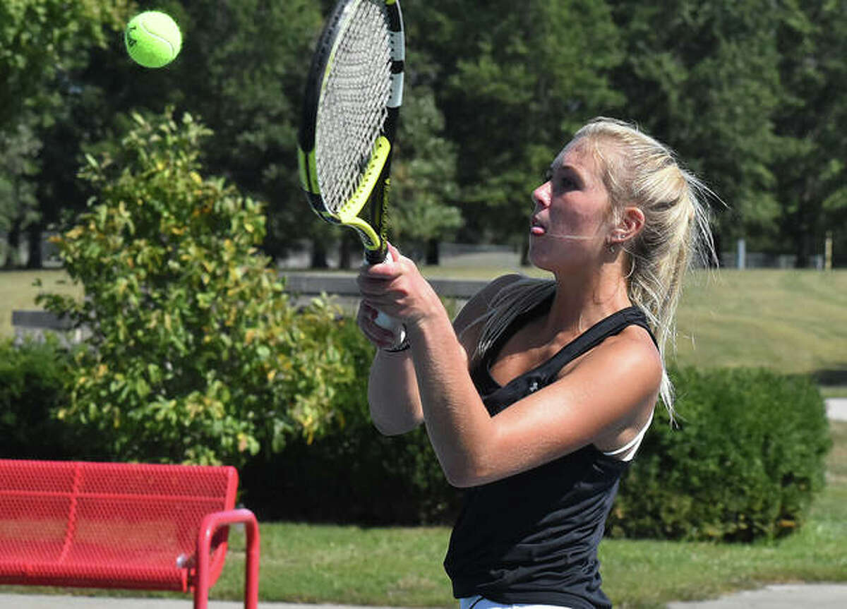 Edwardsville senior Emma Herman reaches up to connect on a backhand shot near the end of her singles match against Marquette on Saturday.