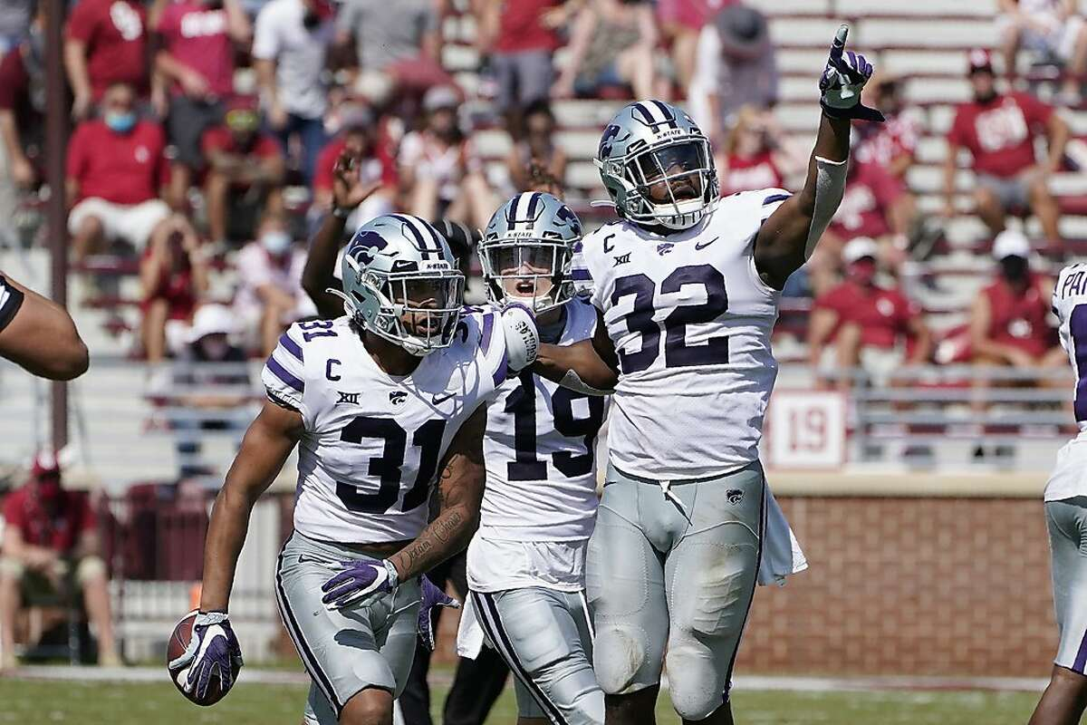 Kansas State defensive back Jahron McPherson (31) celebrates with teammates Ross Elder (19) and Justin Hughes (32) after an interception to seal the win over Oklahoma in the second half of an NCAA college football game Saturday, Sept. 26, 2020, in Norman, Okla. (AP Photo/Sue Ogrocki).