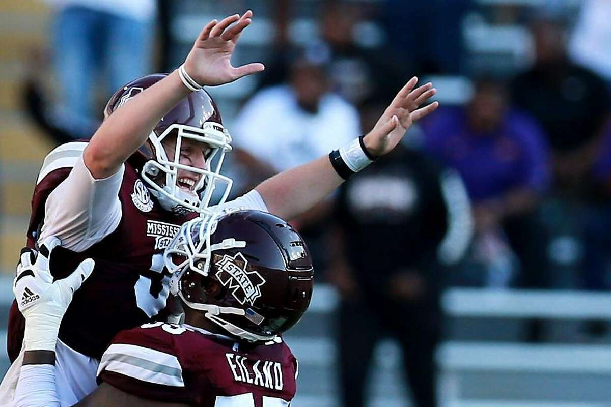 Mississippi State quarterback K.J. Costello, a transfer from Stanfotrd, gets a lift from teammate Greg Eiland after throwing a touchdown pass that helped beat LSU 44-34.