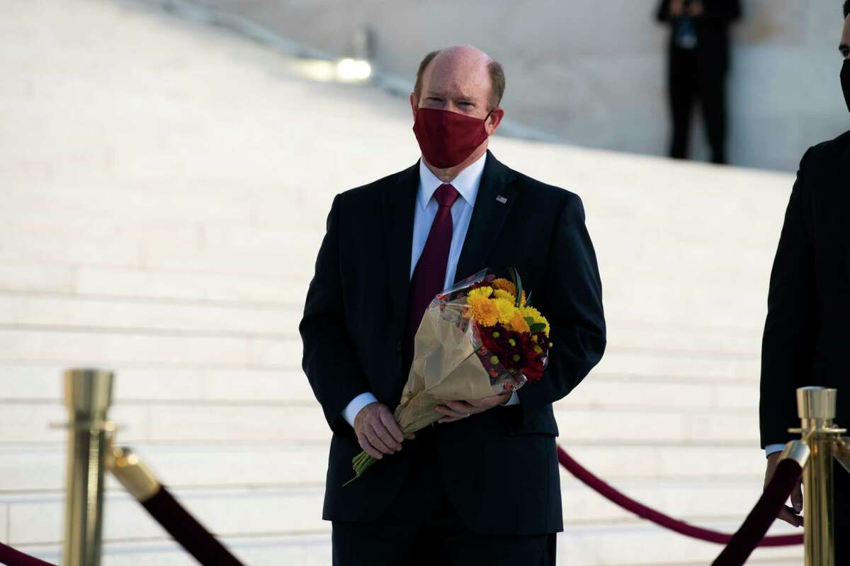 Sen. Chris Coons, D-Del. with flowers pays his respects as Justice Ruth Bader Ginsburg lies in repose under the Portico at the top of the front steps of the U.S. Supreme Court building on Wednesday, Sept. 23, 2020, in Washington. Ginsburg, 87, died of cancer on Sept. 18. (AP Photo/Jose Luis Magana)