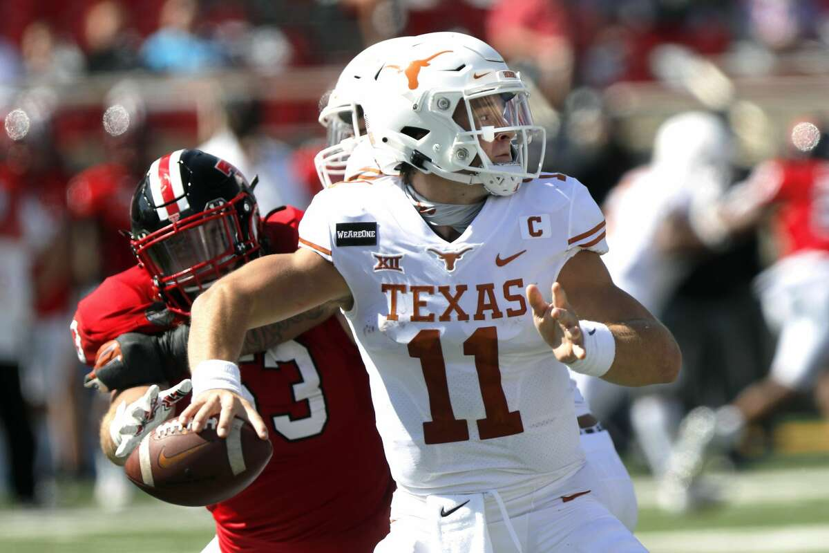Texas quarterback Sam Ehlinger passes downfield under pressure from defensive lineman Eli Howard during the first half of an NCAA college football game against Texas Tech, Saturday Sept. 26, 2020, in Lubbock. (AP Photo/Mark Rogers)