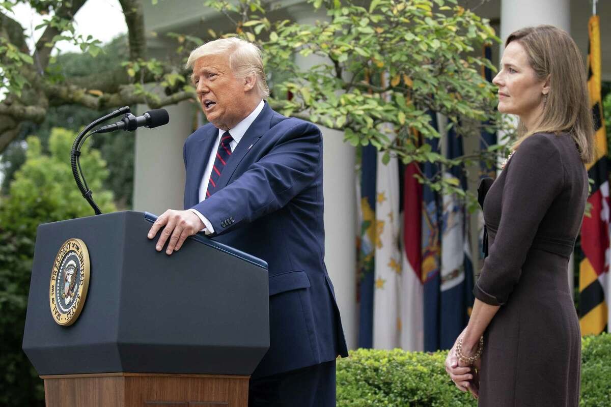 Amy Coney Barrett, U.S. President Donald Trump's nominee for associate justice of the U.S. Supreme Court, right, listens as President Donald Trump speaks during an announcement ceremony in the Rose Garden of the White House in Washington, D.C., U.S., on Saturday, Sept. 26, 2020. Trump said hea€™ll nominate Judge Amy Coney Barrett for the Supreme Court, adding his third justice to the bench and a fresh jolt to his faltering campaign just weeks before Americans vote on whether to give him a second term. Photographer: Stefani Reynolds/Bloomberg