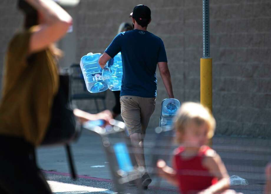 A Walmart customer leaves the store with bottled water in Lake Jackson on Saturday. Photo: Jenna Kieser/The Facts