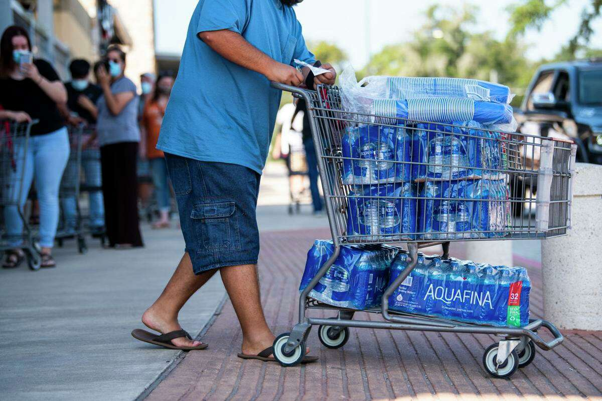 An H-E-B customer leaves with a cart full of bottled water in Lake Jackson on Saturday. Many customers waited in line to purchase water after TCEQ issued a do-not-use order for anyone who gets tap water from Brazosport Water Authority. The order was lifted for every city execpt Lake Jackson.