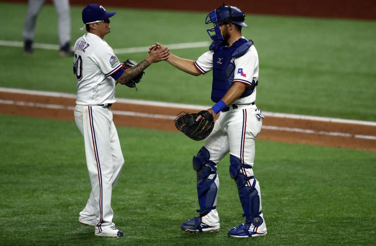 ARLINGTON, TEXAS - SEPTEMBER 26: (L-R) Jesse Chavez #30 and Jeff Mathis #2 of the Texas Rangers celebrate a 6-1 win against the Houston Astros at Globe Life Field on September 26, 2020 in Arlington, Texas. (Photo by Ronald Martinez/Getty Images)