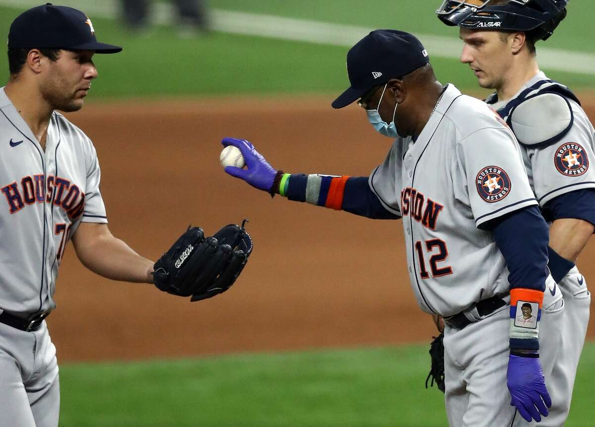 ARLINGTON, TEXAS - SEPTEMBER 26: Manager Dusty Baker #12 gives the ball to Andre Scrubb #70 of the Houston Astros in the seventh inning against the Texas Rangers at Globe Life Field on September 26, 2020 in Arlington, Texas. (Photo by Ronald Martinez/Getty Images)