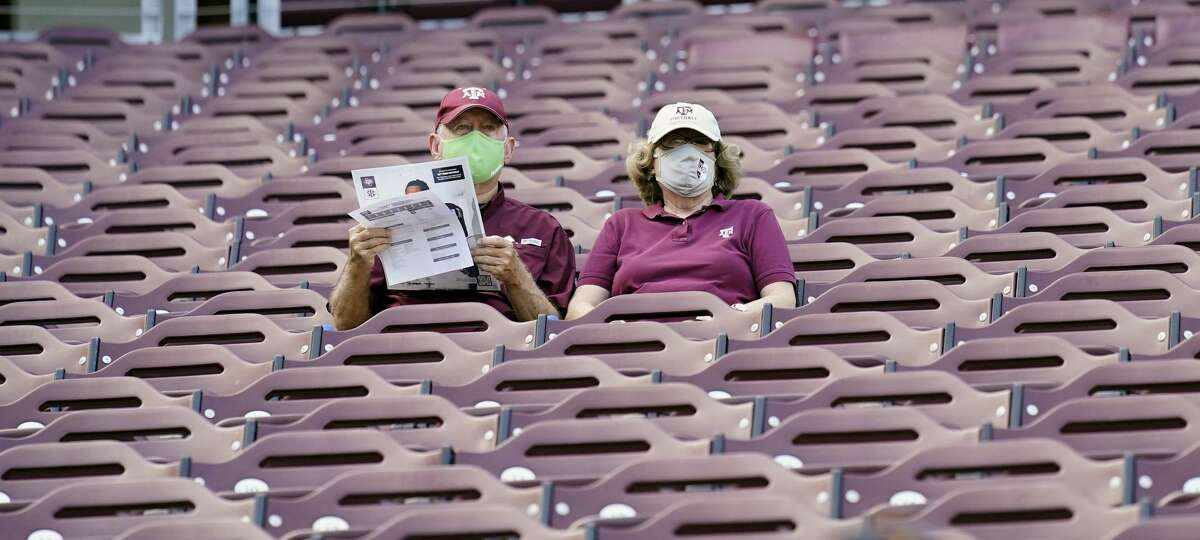Fans wear masks as they sit in the stands at Kyle Field before an NCAA college football game between Vanderbilt and Texas A&M Saturday, Sept. 26, 2020, in College Station, Texas. (AP Photo/David J. Phillip)