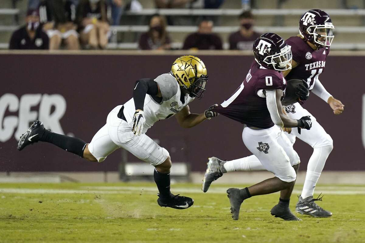 Vanderbilt defensive back Donovan Kaufman (1) grabs the jersey of Texas A&M running back Ainias Smith (0) during the first half of an NCAA college football game Saturday, Sept. 26, 2020, in College Station, Texas. (AP Photo/David J. Phillip)